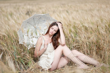 Beautiful sad and lonely woman with umbrella sitting in wheat field. Timed. photo