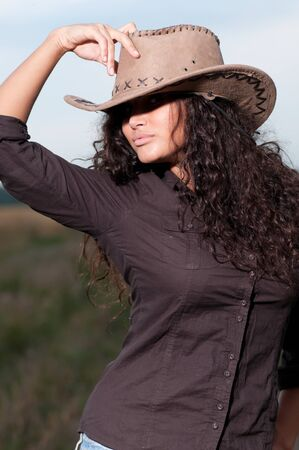 Beautiful cowboy woman with perfect hair and skin posing in country field Stock Photo - 8876168