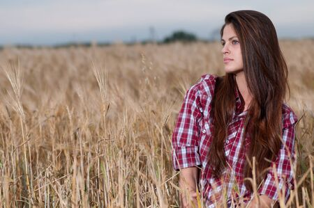 Beautiful cowboy woman with perfect hair and skin posing in country field photo