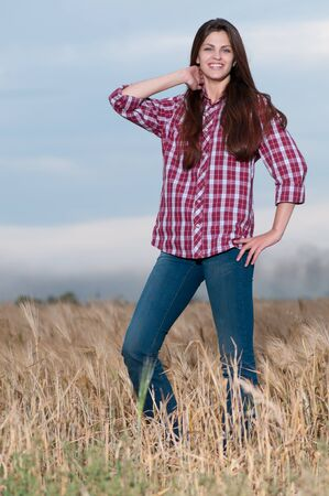 Beautiful cowboy woman with perfect hair and skin posing in country field Stock Photo - 8876165