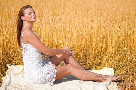 Beautiful woman in white dress with perfect hair and skin posing in wheat field on sunny summer day. Picnic. photo