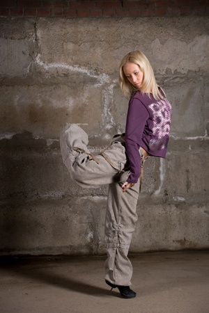 Beautiful hip hop girl dancing over grey brick wall Stock Photo - 8877489