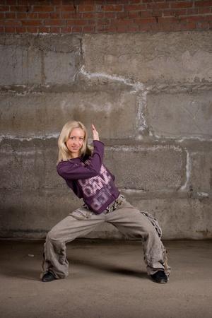 Beautiful hip hop girl dancing over grey brick wall photo
