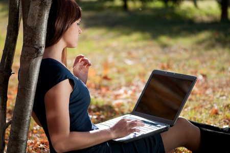 Young business woman using notebook mobile computer at city park. Working student photo