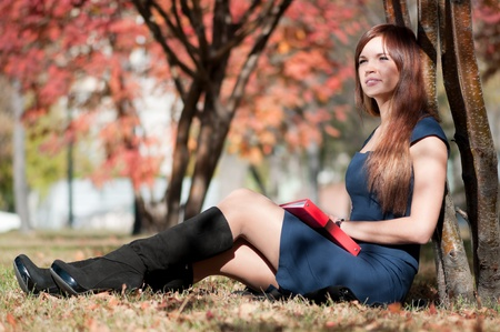 Young business woman planing, writing and reviewing  diary at city park. Student photo