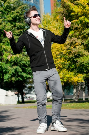 young casual cheerful man dancing outdoor in city park photo