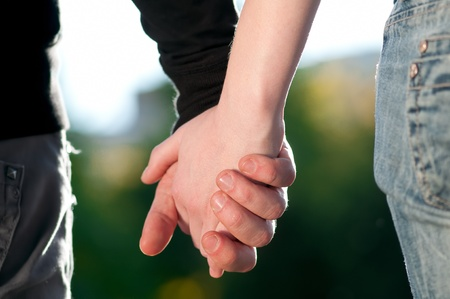 Concept shoot of friendship and love of man and woman: two hands over sun ray and nature Stock Photo - 8945689