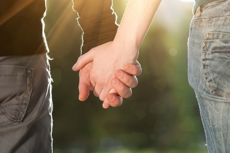 Concept shoot of friendship and love of man and woman: two hands over sun ray and nature Stock Photo - 8948966