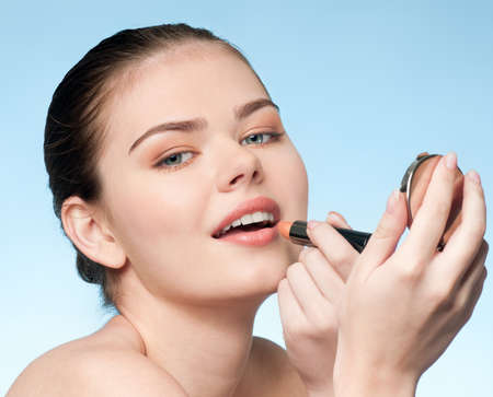 Beautiful young adult woman applying cosmetic lipstick - close-up portrait photo