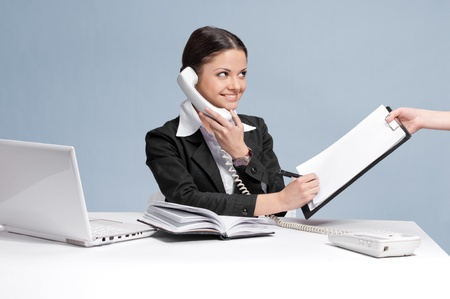 Busy business woman in office talking by phone and sign a papers at work place. Cheerful photo