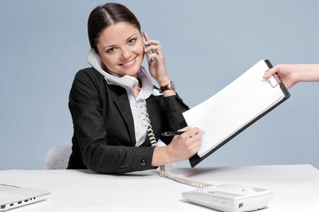 Busy business woman in office talking by two phones and sign a papers at work place. Smile photo