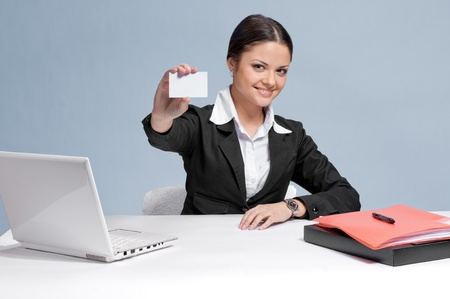 Emotional business woman in office palce show white personal card. Smile