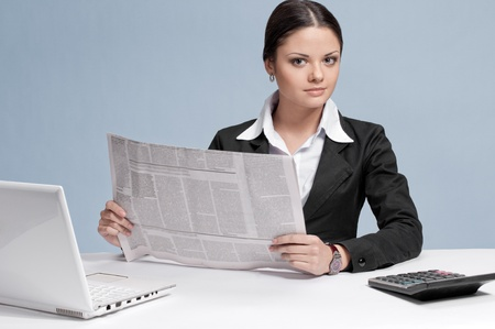 Busy business woman with frash newspaper over white table and laptop. Sure photo