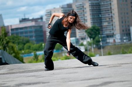 Beautiful teenage girl dancing hip-hop over urban city landscape photo