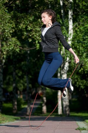 skipping: Beautiful young woman doing  exercise with skipping rope at park. Jumping