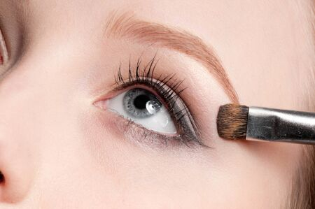 Beautiful young adult woman applying cosmetic paint brush - close-up portrait of eye shadow zone Stock Photo - 8949126