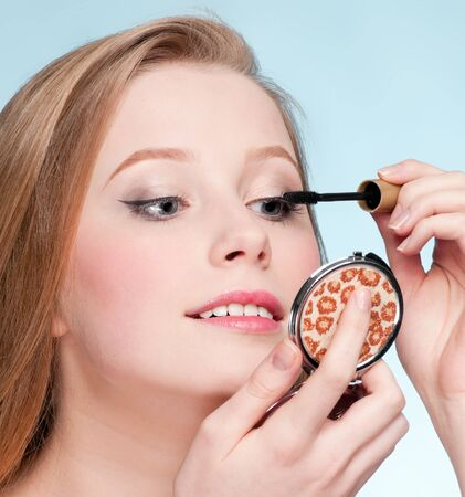 Beautiful young adult woman applying cosmetic mascara brush - close-up portrait of eyes zone photo
