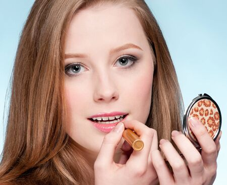 Beautiful young adult woman applying cosmetic lipstick - close-up portrait Stock Photo - 8949125
