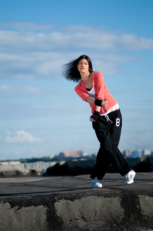 Beautiful woman dancing hip-hop modern style over urban city landscape and blue sky Stock Photo - 9068319