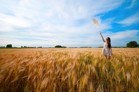 Beautiful sad and lonely woman with umbrella walking in wheat field. Timed. Stock Photo - 9068792