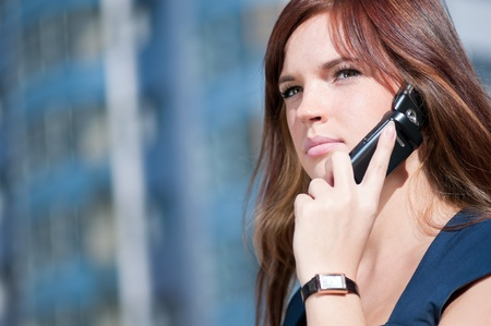 Young business woman using mobile cell phone over city background. Student photo