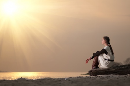 Beautiful young lonely woman sitting on sea coast at autumn sunset