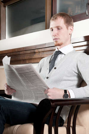 Sure young business man in office rest room  interior with fresh newspaper Stock Photo - 9109206