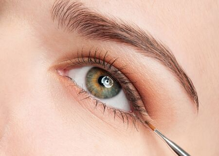 Beautiful young adult woman applying cosmetic paint brush - close-up portrait of eye shadow zone Stock Photo