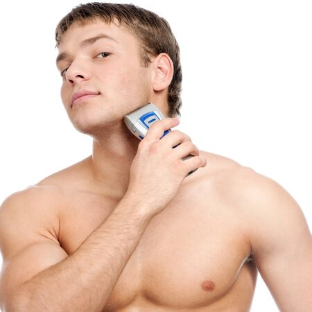 electric shaver: Portrait of a young handsome man shaving as part of his morning routin