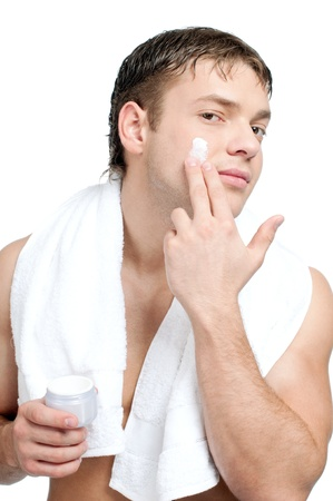 Man putting on cream lotion on face Stock Photo