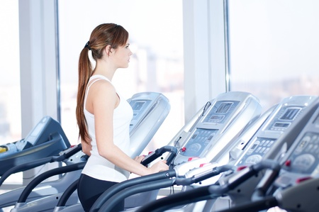 kardio: Young woman at the gym exercising. Run on on a machine.