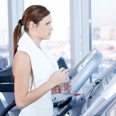 Young woman at the gym exercising. Run on on a machine and drink water photo