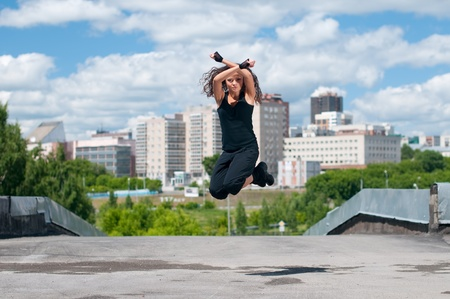 Beautiful teenage girl dancing in modern style over urban city landscape photo