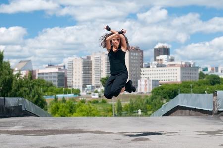 Beautiful teenage girl dancing in modern style over urban city landscape photo