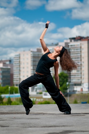 Beautiful teenage girl dancing in modern style over urban city landscape Stock Photo - 9219698