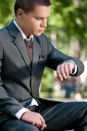 Young business man waiting for meeting at green park and looks at the watch. Student. Stock Photo - 9219716