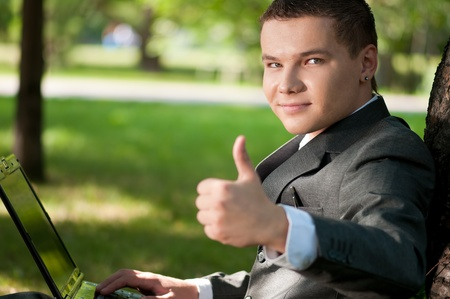 Young business man working on notebook laptop computer, at green park. Student. Thumbs up! Stock Photo - 9219662