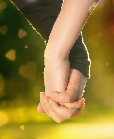 Concept shoot of friendship and love of man and woman: two hands over sun ray and nature Stock Photo - 9219254