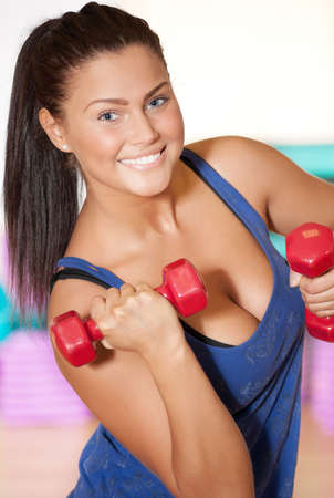 Beautiful sport woman doing power fitness exercise at sport gym. Dumbbell photo