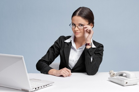 Casual business woman in office working with white table, laptop and phone photo
