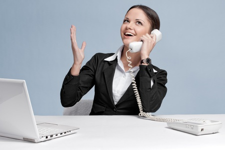 Casual business woman in office working with white table, laptop and talking by phone. Excellent! photo