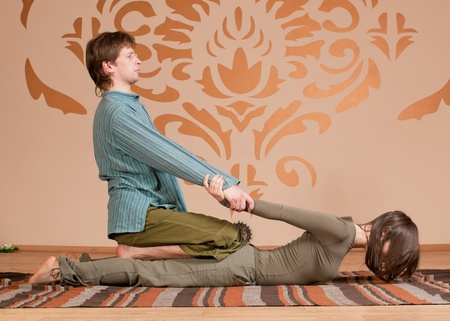Two young man and woman couple doing yoga. Massage Stock Photo