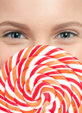 Pretty young woman with lollipop isolated on the white background photo