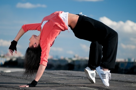 hiphop: Beautiful woman dancing hip-hop modern style over urban city landscape and blue sky