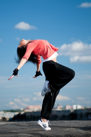 woman dancing: Beautiful woman dancing hip-hop modern style over urban city landscape and blue sky