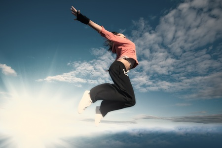 Beautiful sport woman in urban sportswear jumping and fly over blue sky with clouds and sun beam Stock Photo