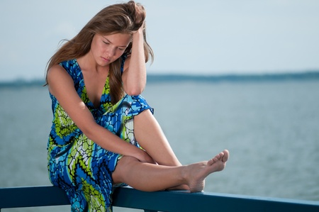 Beautiful sad woman in dress sitting  over sea at summer storm day