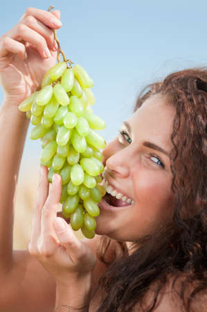 Beautiful woman with perfect hair and skin posing in wheat field and eating green grapes. Picnic. Stock Photo - 9293295