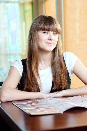 A young attractive woman sitting in a cafe with menu photo