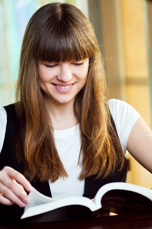 A young attractive woman sitting in a cafe. Reading book photo